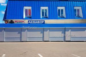 Торговый ряд с рекламным фризом в Анискино. Рольставни на окна и на двери. Вид с фасада